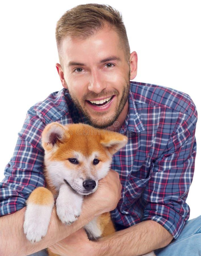 Jonge mens met leuk weinig Akita Inu-puppy stock afbeelding