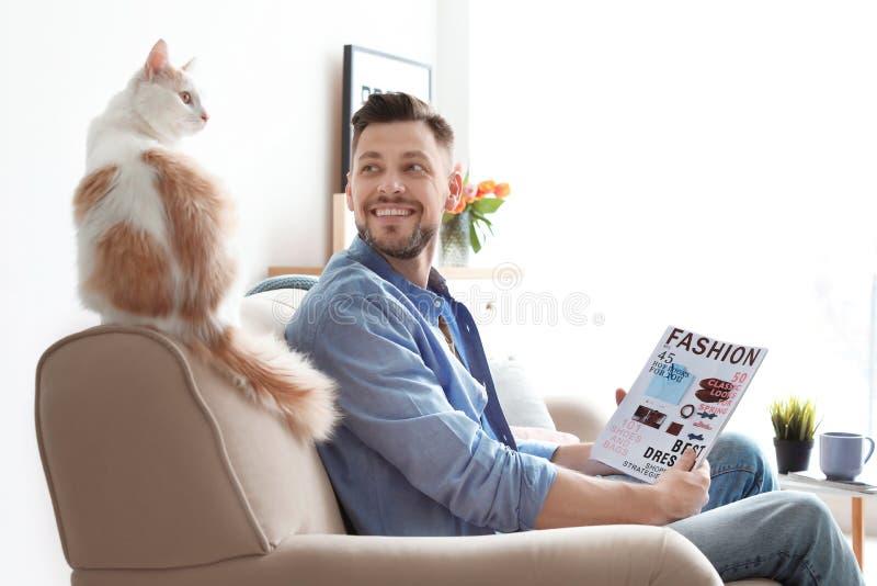 Jonge mens met leuke kat op bank stock fotografie