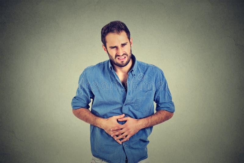 Jonge mens met maagpijn stock foto's