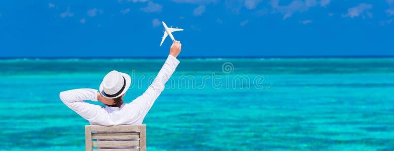 Jonge mens met miniatuur van een vliegtuig bij royalty-vrije stock afbeelding