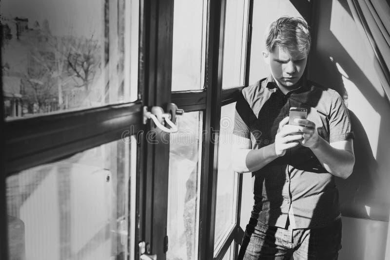 Jonge mens met mobiel telefoonverblijf dichtbij de venster in tegenstelling dag royalty-vrije stock afbeelding