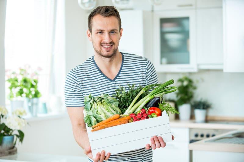 Jonge mens met plantaardige doos in keuken royalty-vrije stock afbeelding