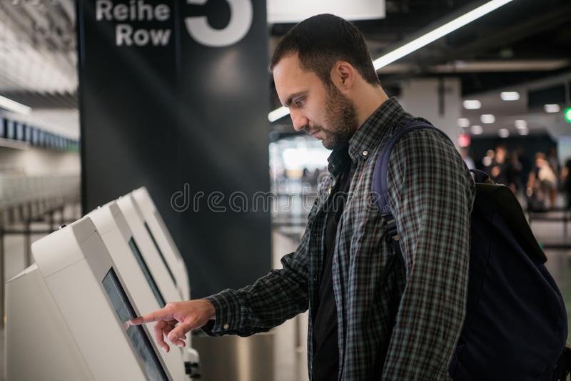Jonge mens met rugzak wat betreft interactieve vertoning die zelfbedieningsmachine met behulp van, die zelf-controle-binnen voor  royalty-vrije stock afbeeldingen