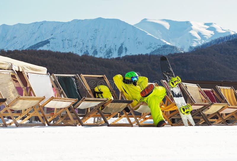 Jonge mens met snowboard zitting en het ontspannen stock foto's