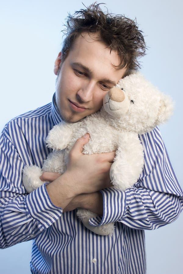 Jonge mens met teddy stock afbeelding