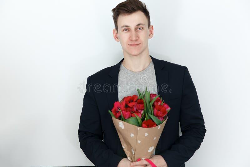 Jonge mens met tulpen, boeket van de lentebloemen stock foto