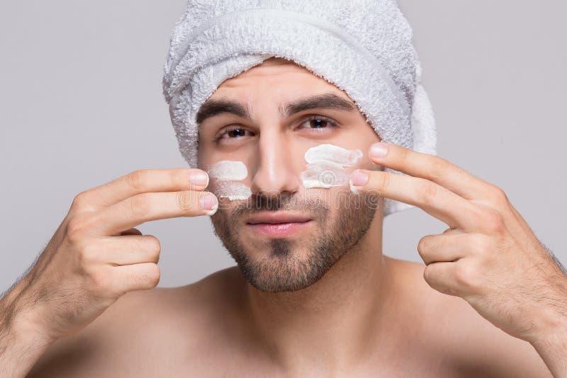 Jonge mens met vochtinbrengende crèmeroom op het gezicht stock foto