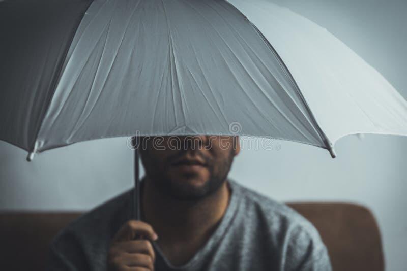 Jonge mens met witte parapluzitting op een bank thuis - Veiligheidsconcept - om risico'sconcept niet te nemen royalty-vrije stock foto's
