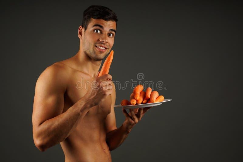 Jonge mens met wortelen royalty-vrije stock afbeelding