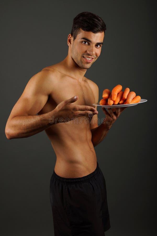 Jonge mens met wortelen stock foto's