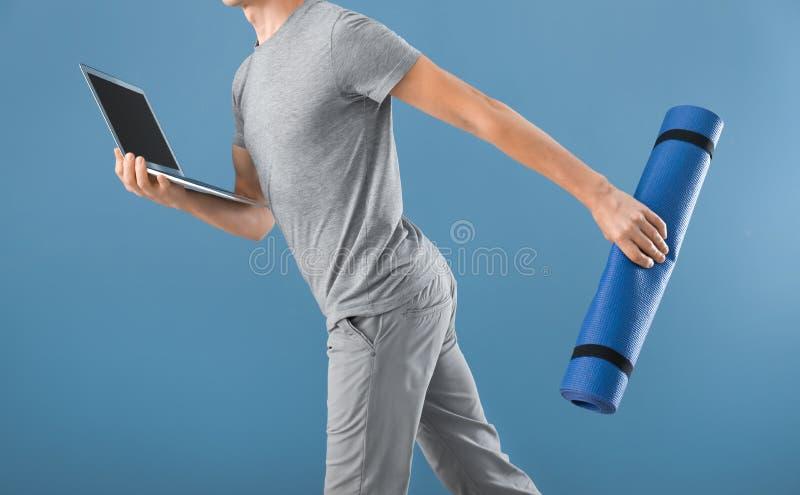 Jonge mens met yogamat en laptop die op kleurenachtergrond lopen Concept evenwicht tussen rust en het werk royalty-vrije stock foto