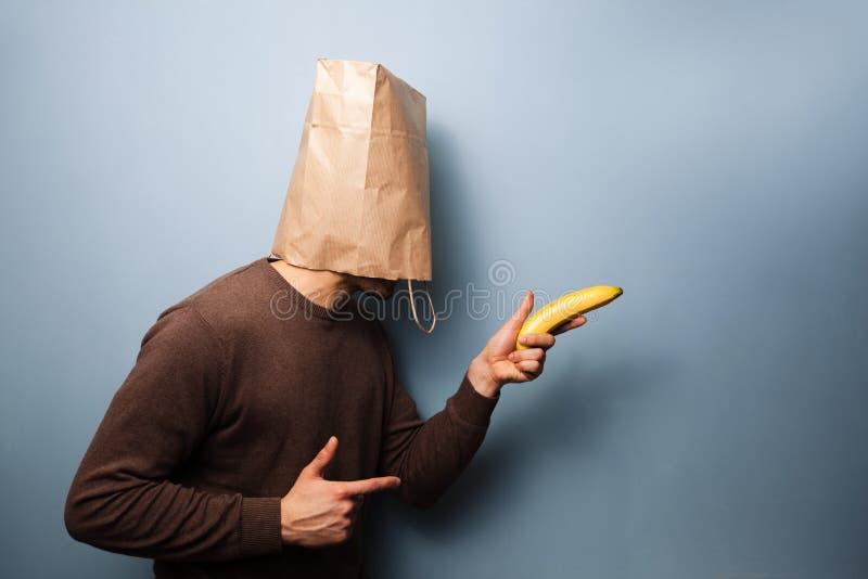 Jonge mens met zak over zijn hoofd gebruikende banaan als kanon royalty-vrije stock afbeeldingen