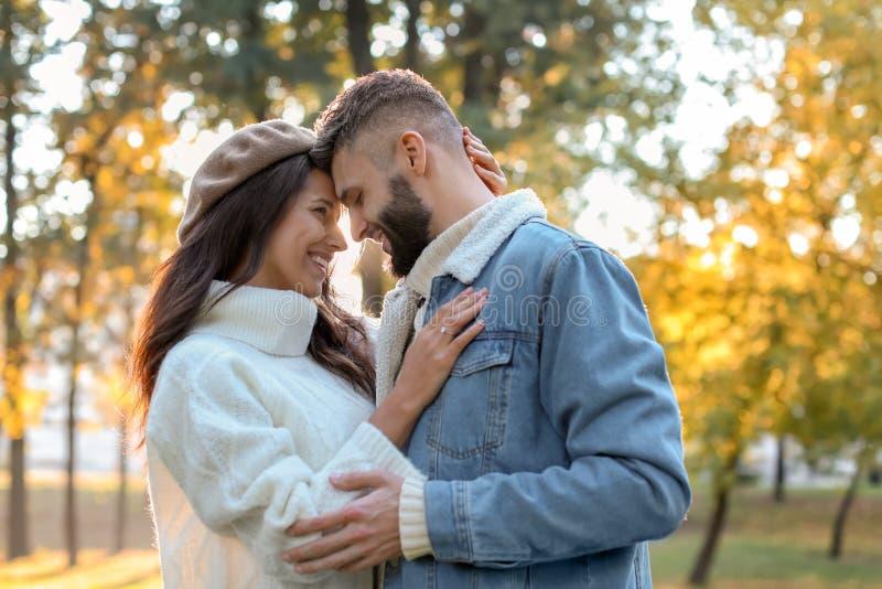 Jonge mens met zijn geliefde dragende verlovingsring in de herfstpark stock foto's