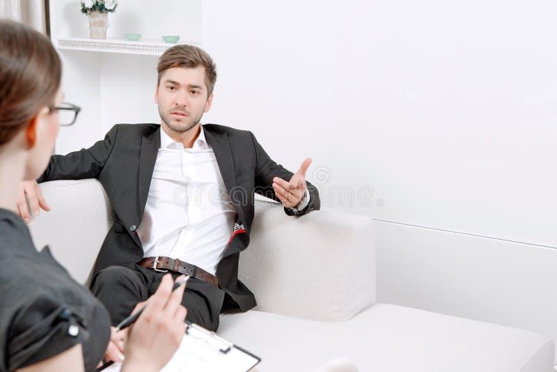 Jonge mens met zijn psycholoog stock fotografie