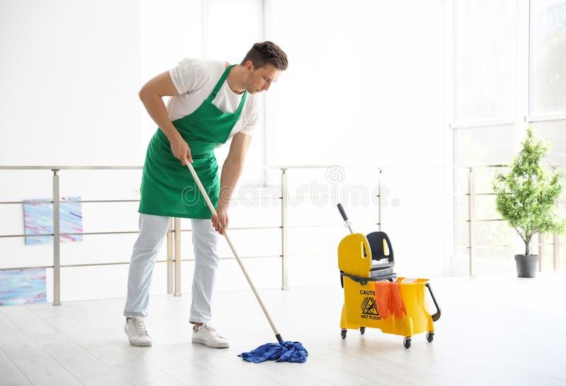 Jonge mens met zwabber schoonmakende vloer stock afbeelding