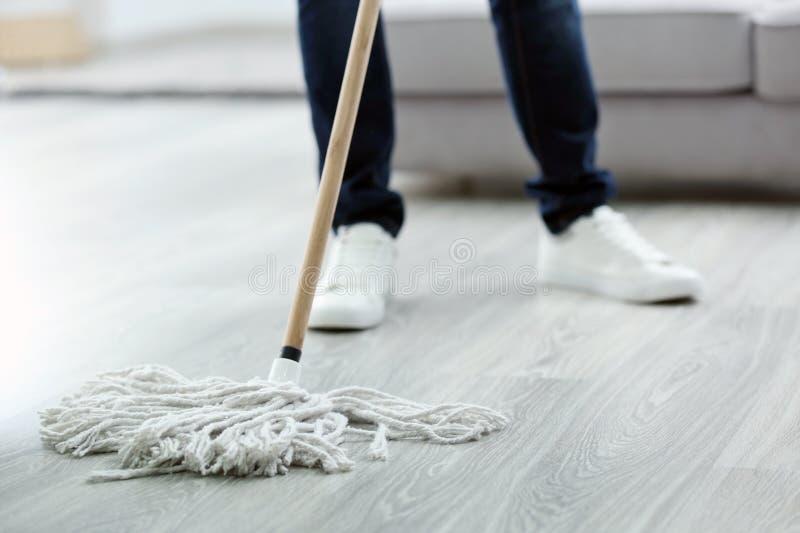 Jonge mens met zwabber schoonmakende vloer thuis stock foto