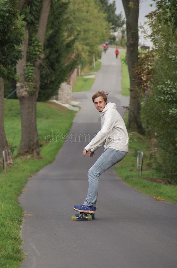 Jonge mens op een longboard die onderaan een lege weg drijven stock afbeelding