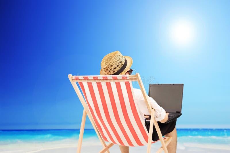 Jonge mens op een openluchtstoel die aan laptop, naast een overzees werken stock fotografie