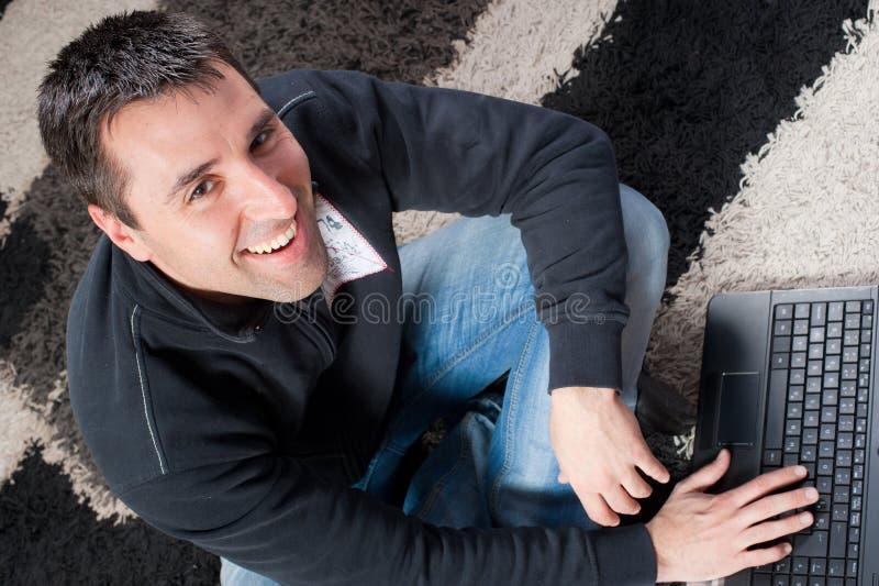 Jonge mens op een tapijt met laptop royalty-vrije stock foto's