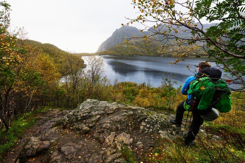 Jonge mens op een wandelingsreis op de Lofoten-Eilanden in Noorwegen die zich op een klippenrand en blikken over een meer in de a royalty-vrije stock afbeelding