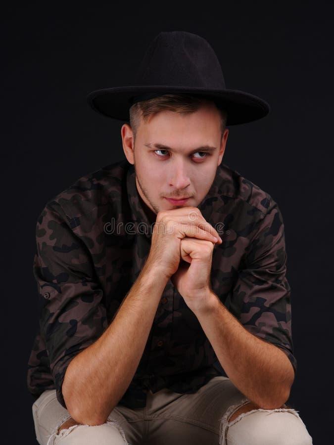 Jonge mens op een zwarte achtergrond met een hoed royalty-vrije stock foto's
