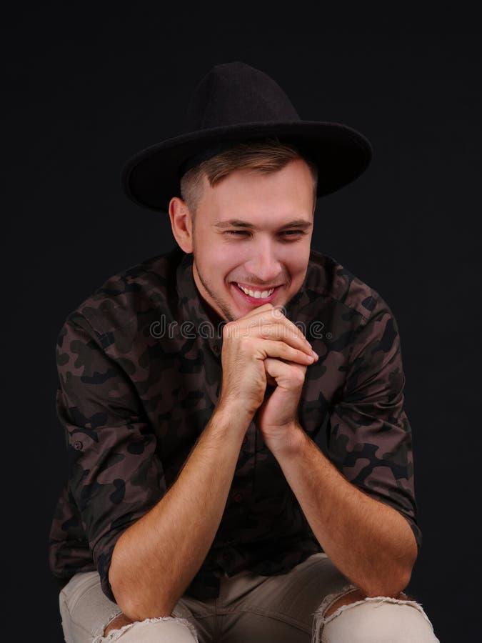 Jonge mens op een zwarte achtergrond met hoed glimlachen verknoeid zijn ogen stock fotografie