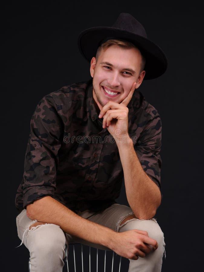 Jonge mens op een zwarte achtergrond met hoed het glimlachen royalty-vrije stock afbeeldingen