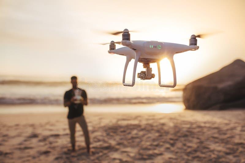 Jonge mens op het strand die een hommel vliegen stock afbeelding