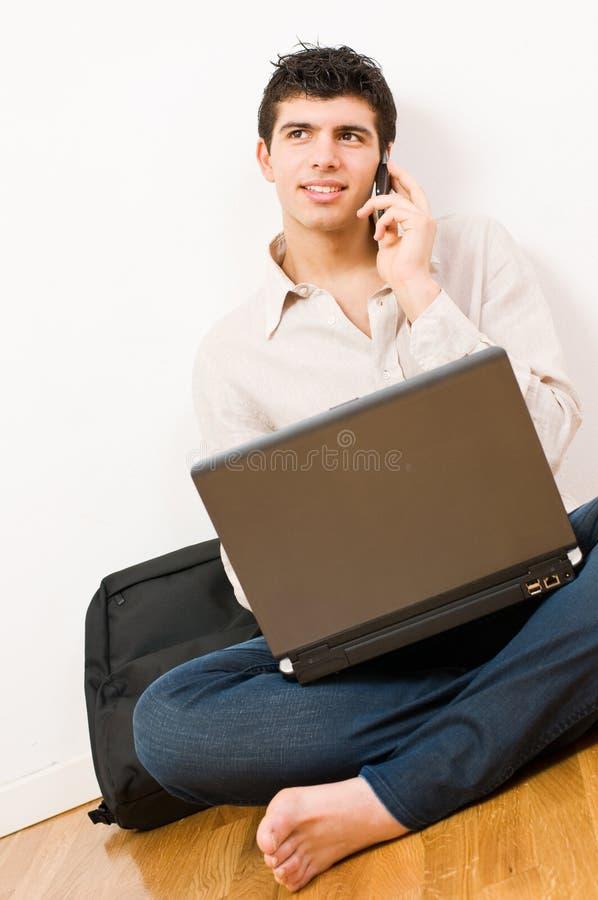 Jonge mens op laptop en mobiel stock fotografie