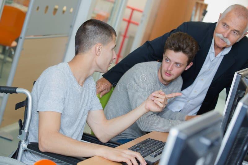 Jonge mens op rolstoel tijdens computerklasse stock foto