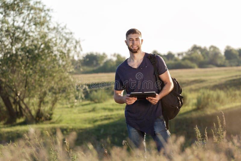 Jonge mens op stijging in aard die digitale tablet gebruiken stock afbeeldingen