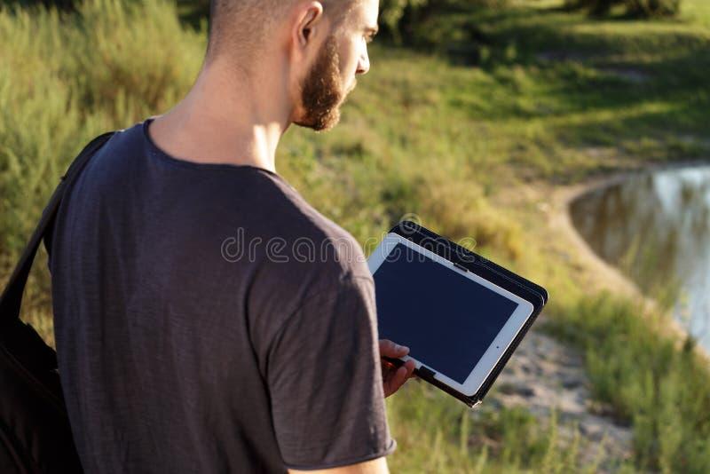 Jonge mens op stijging in aard die digitale tablet gebruiken royalty-vrije stock foto