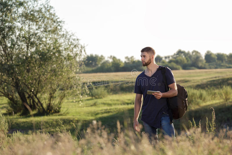 Jonge mens op stijging in aard die telefoon met behulp van stock afbeeldingen