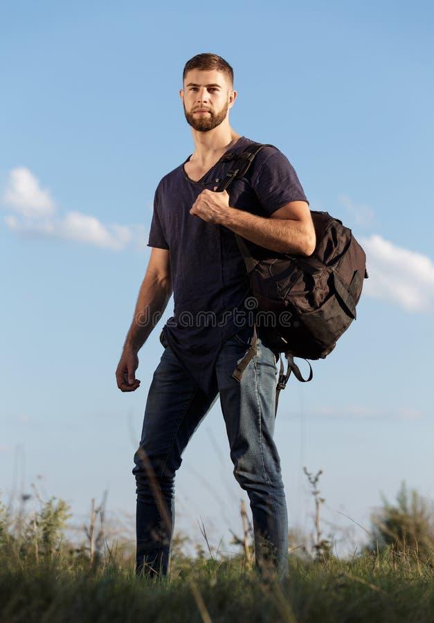 Jonge mens op stijging in aard met rugzak stock foto