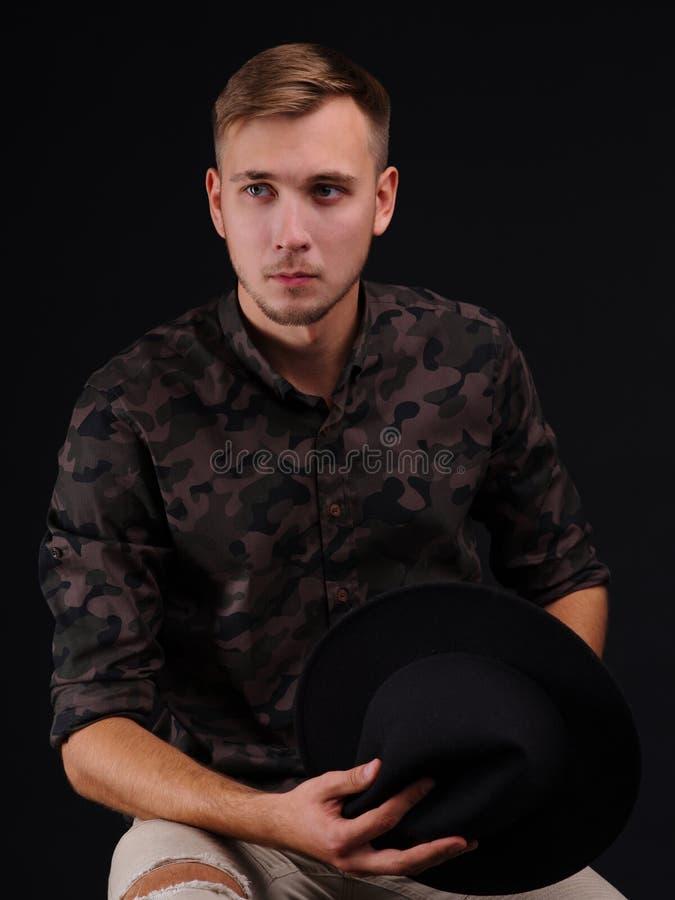 Jonge mens op zwarte achtergrond met hoed in handen royalty-vrije stock fotografie