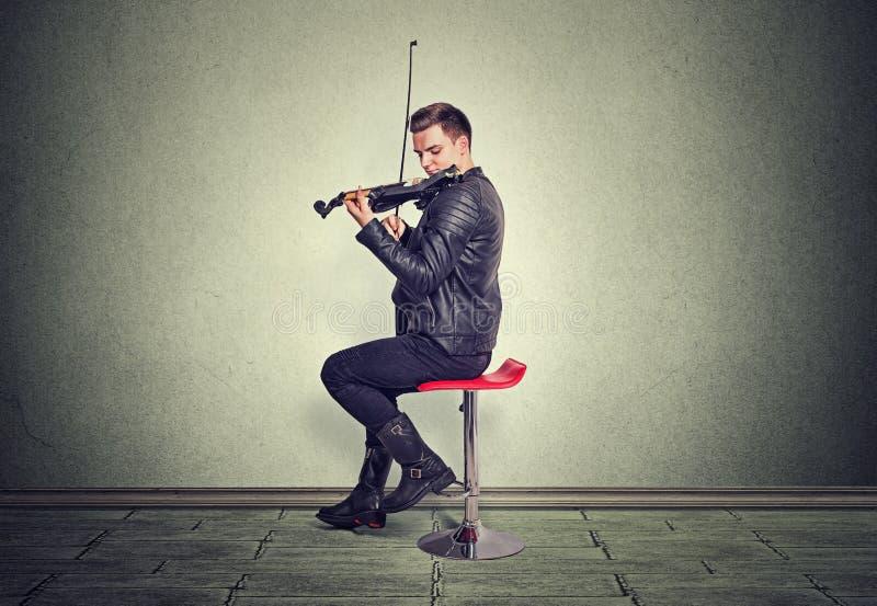 Jonge mens op zwarte houten viool stock afbeelding