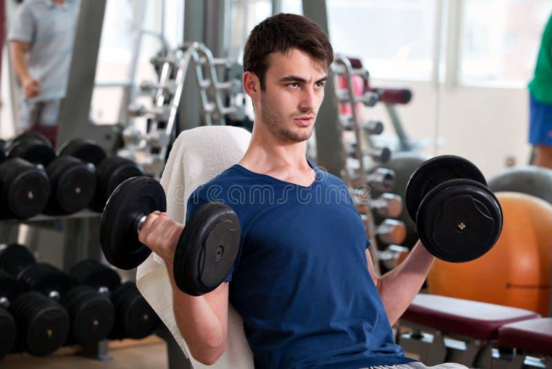 Jonge mens opleiding in de gymnastiek stock foto's
