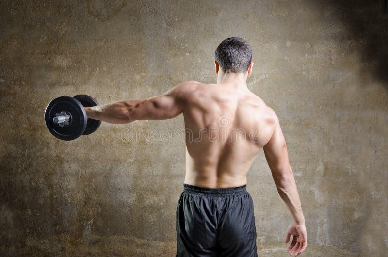 Jonge mens opleidingsgewichten in od gymnastiek stock afbeeldingen