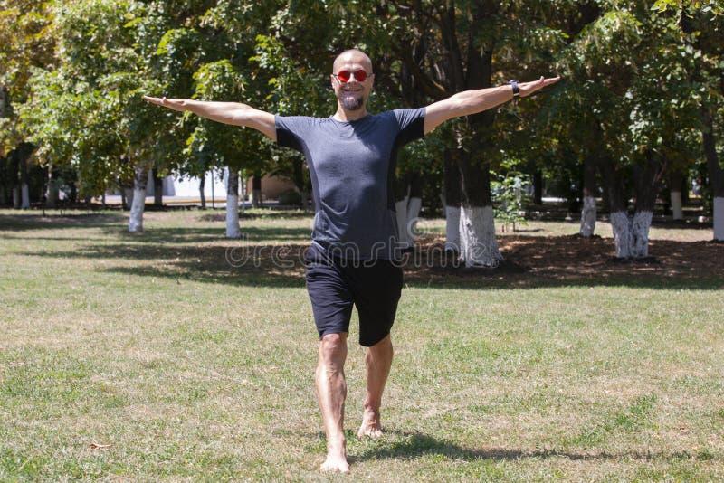 Jonge mens opleidingsyoga in openlucht De sportieve kerel maakt uitrekkende oefening op een blauwe yogamat, op de sportengrond royalty-vrije stock foto's