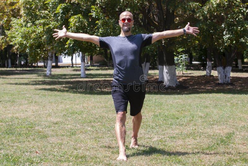 Jonge mens opleidingsyoga in openlucht De sportieve kerel maakt uitrekkende oefening op een blauwe yogamat, op de sportengrond royalty-vrije stock afbeelding