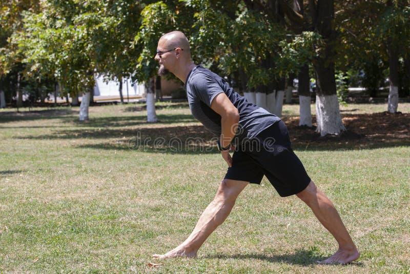 Jonge mens opleidingsyoga in openlucht De sportieve kerel maakt uitrekkende oefening op een blauwe yogamat, op de sportengrond stock foto's