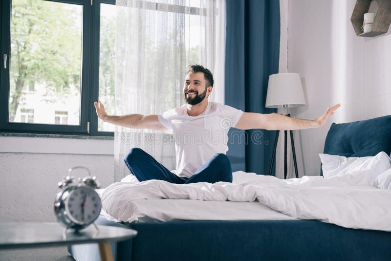 Jonge mens in pyjama's die terwijl het zitten op bed bij ochtend uitrekken zich royalty-vrije stock foto's
