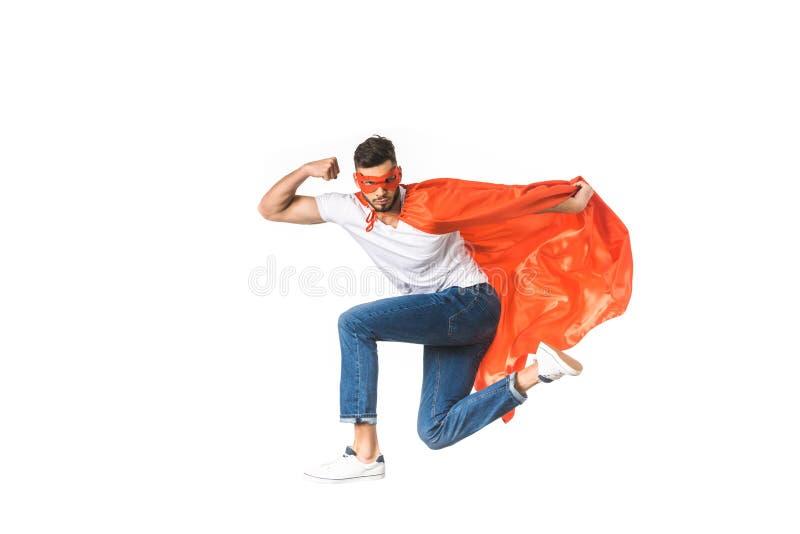 jonge mens in rode mantel en masker die camera bekijken en bicepsen tonen royalty-vrije stock foto's
