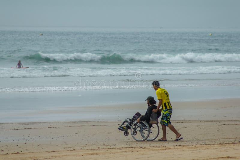 Jonge mens in rolstoel en zijn frend op de weg aan het strand branding royalty-vrije stock afbeelding