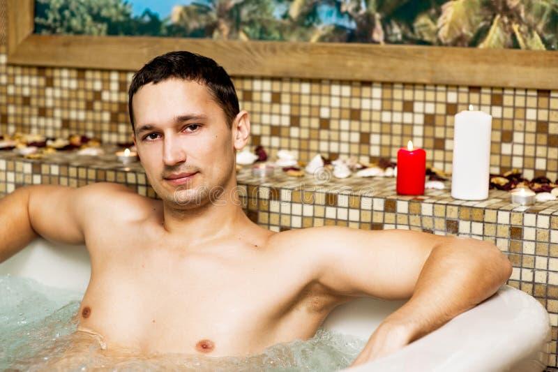Jonge mens in romantische Jacuzzi stock foto's