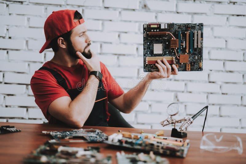 Jonge Mens in Rood GLB met Gebroken Motherboards stock afbeelding