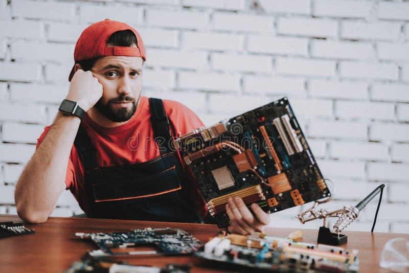 Jonge Mens in Rood GLB met Gebroken Motherboards stock afbeeldingen
