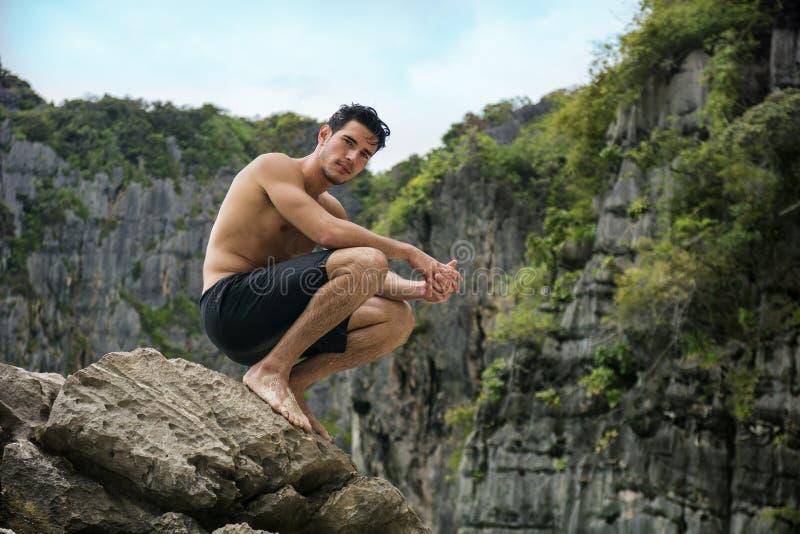 Jonge mens shirtless status, heuvels op achtergrond stock foto's