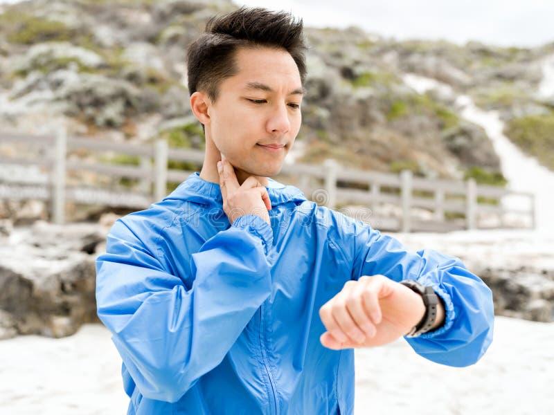 Jonge mens in sportkleding die smartwatch gebruiken royalty-vrije stock fotografie