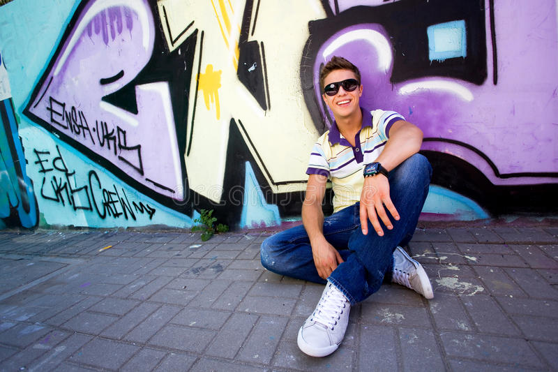Jonge mens tegen graffitimuur stock fotografie